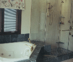 remodeled bathroom with glass shower and corner bathtub